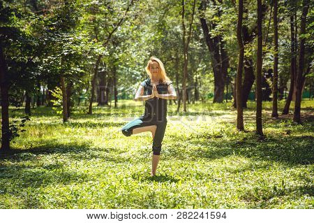 Vrikshasana. Yoga Asanas In Nature. Yoga Poses Everyday. Practicing Young Woman. Yoga In The Park