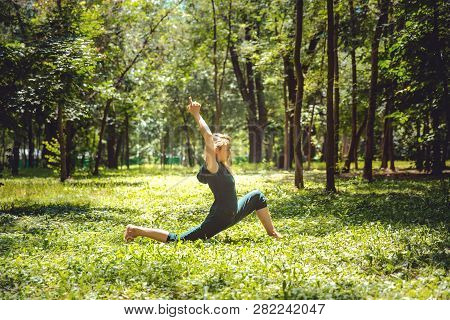 Anjaneyasana. Yoga Asanas In Nature. Yoga Poses Everyday. Practicing Young Woman. Yoga In The Park
