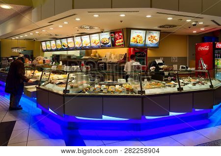 Prague, Czech Republic - January 25, 2019: Unknown Man Examines Food At Counter In Food Court Area I
