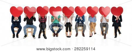 large group of people holding big red hearts over their faces, celebbrating valentine's day together, on white background