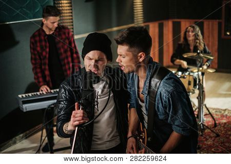 Music band having rehearsal in a studio