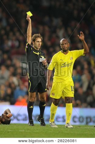 BARCELONA - NOV 13: Referee Delgado Ferreiro delivers yellow card to Senna of Villareal during spanish league match against FC Barcelona at Nou Camp Stadium on November 13, 2010 in Barcelona, Spain
