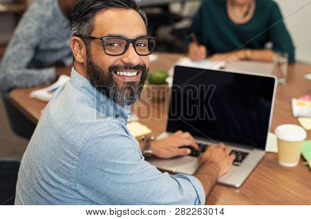 Mature middle eastern businessman using laptop at desk in busy office.Happy smiling casual man looking at camera while sitting at table and working on laptop computer. Indian leader using laptop.