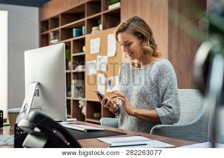Beautiful smiling woman reading text message on mobile phone. Mature businesswoman checking new messages on smartphone. Casual businesswoman checking important mail while working on computer in office