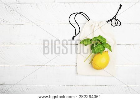 Lemon And Basil On White Cotton Eco Bag On White Wooden Background. The Concept Of No Plastic Zero W
