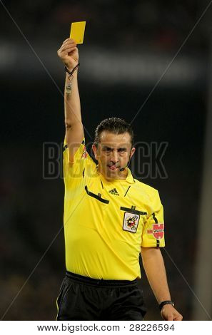 BARCELONA - FEB 20: Referee Ramirez Dominguez delivers yellow card during the match between FC Barcelona and Athletic de Bilbao at the Nou Camp Stadium on February 20, 2011 in Barcelona, Spain