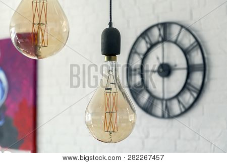Decorative Antique Edison Style Light Bulbs Against Brick Wall Background And Clock
