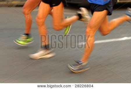 Marathon runners legs on the road followed by another runner with panning blur