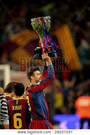 BARCELONA - MAY 15: Gerard Pique of Barcelona celebrates and holds up the trophy league at Nou Camp Stadium in Barcelona, Spain on May 15, 2011