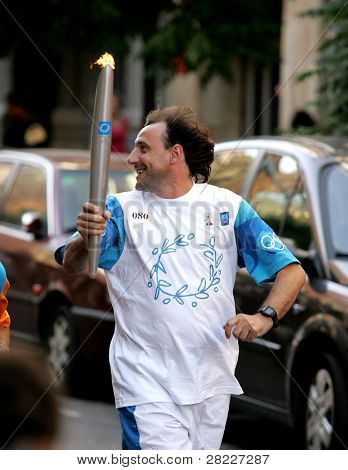 BARCELONA - JUNE 28: Spanish athlete Fermin Cacho carries the Athens 2004 Olympic torch during the Barcelona Torch Route through the city streets, June 28, 2004 in Barcelona, Spain