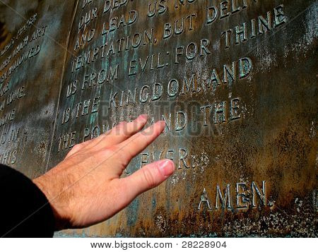 Hand reaching out to sculpture of the Lord's Prayer