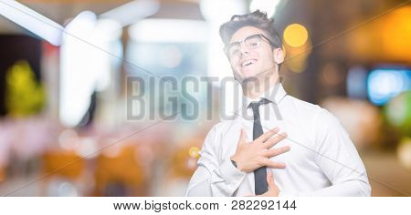 Young business man wearing glasses over isolated background Smiling and laughing hard out loud because funny crazy joke. Happy expression.