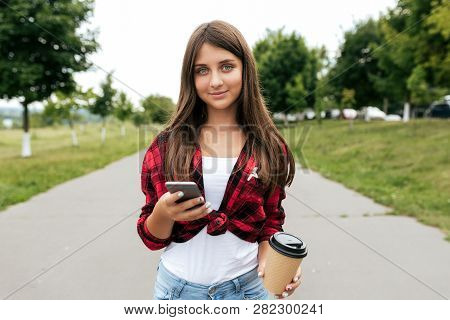 Beautiful Girl With Long Hair Teenager 11-12 Years Old, Standing In Summer In City Park. In Hands Of