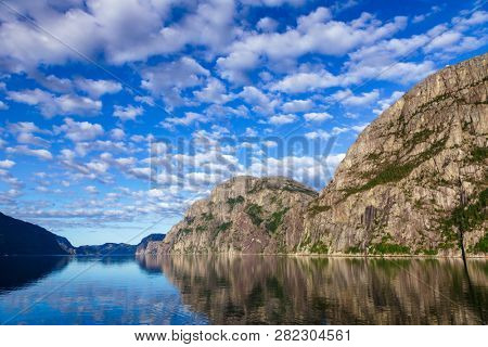 Cloudy sky over calm Lysefjord (Lysefjorden) fjord, a popular travel destination in Forsand municipality of Rogaland county, Norway, Scandinavia