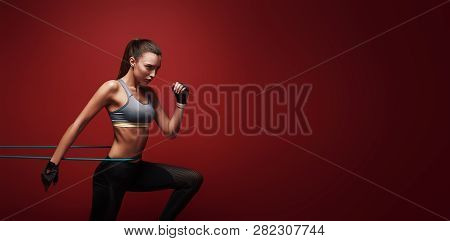 Never Give Up. Sportswoman Performs Exercises With Resistance Band Over Red Background