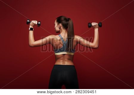 Determined To Win. Sportswoman Holds Dumbbells Standing Over Red Background