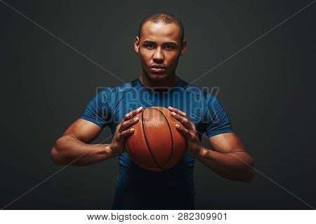 Ready To Play. Handsome Sportsman Standing Over Dark Background Holding Basketball Ball In His Hands