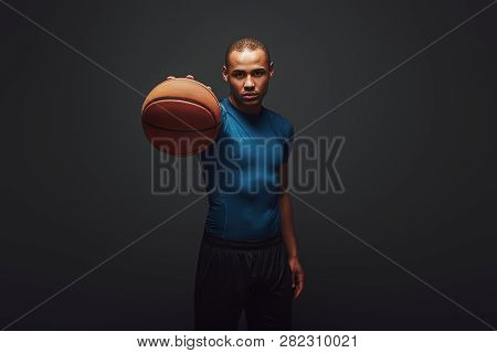 Keep It Up. Handsome Sportsman Standing Over Dark Background With Basketball Ball In His Hand