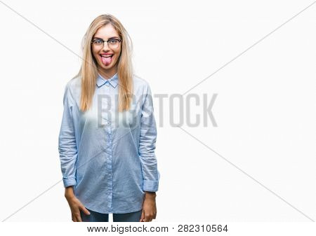 Young beautiful blonde business woman wearing glasses over isolated background sticking tongue out happy with funny expression. Emotion concept.