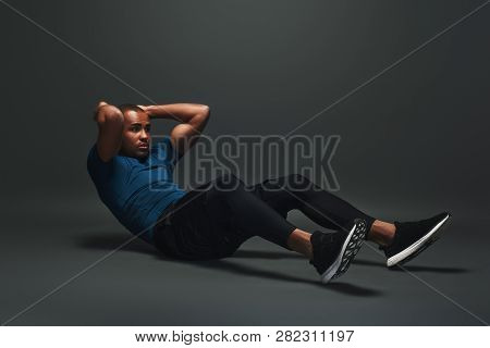 Strong Body. Sportsman Lying Over Dark Background, Working Abs