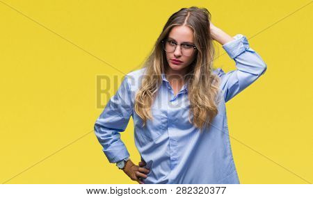 Young beautiful blonde business woman wearing glasses over isolated background confuse and wonder about question. Uncertain with doubt, thinking with hand on head. Pensive concept.