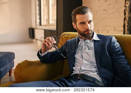 Handsome And Stylish...young Businessman In Fashion Suit Is Holding Glasses, Sitting On Sofa And Thi