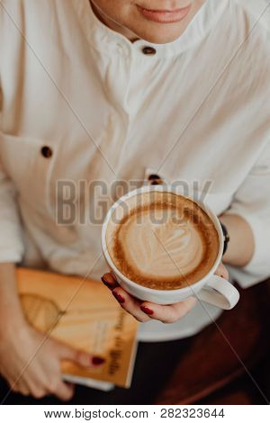 Artsy girl having a cup of coffee