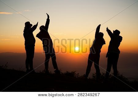 Silhouette Of Young Woman Are Standing On Top Of The Mountain With Raised Hands Relaxing With Sunris