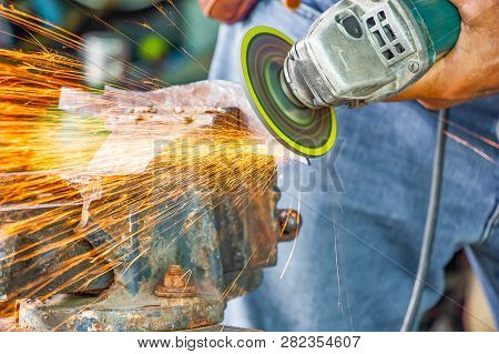 Close Up Hand And Electric Wheel Grinding On Steel Structure In Factory,sparks From The Grinding Whe