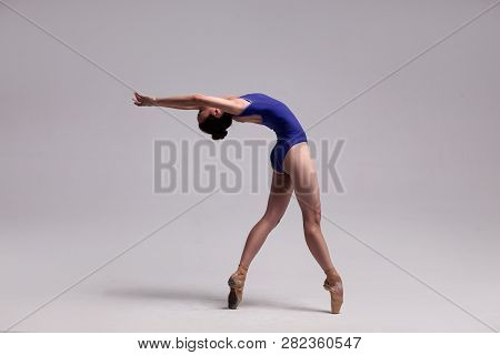Beautiful Ballet Dancer Posing On Pointes. Ballerina Wearing Blue Swimsuit And Beige Pointe Shoes Is