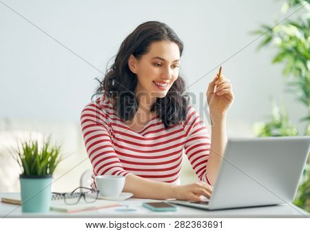 Happy casual beautiful woman working on a laptop at home.