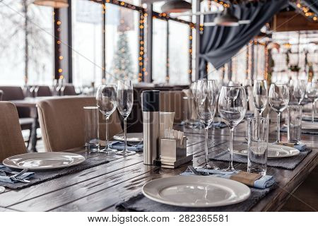 Restaurant Serving, Glass Wine And Water Glasses, Plates, Spice Set, Forks And Knives On Textile Nap