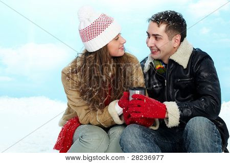 Portrait of amorous couple drinking hot tea on winter day