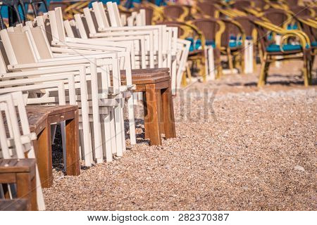 Pile Of Wooden Chairs Piled Up On The Beach Outside The Seaside Restaurant