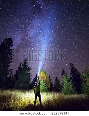 Silhouette of climber standing against the Milky Way with a flashlight in his hands. Location Carpathian, Ukraine, Europe. Astrophotography of milkyway. Dramatic scene. Discover the beauty of earth.