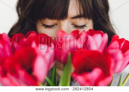 Beautiful Brunette Girl Portrait With Red Tulips Closeup On White Background Indoors, Space For Text