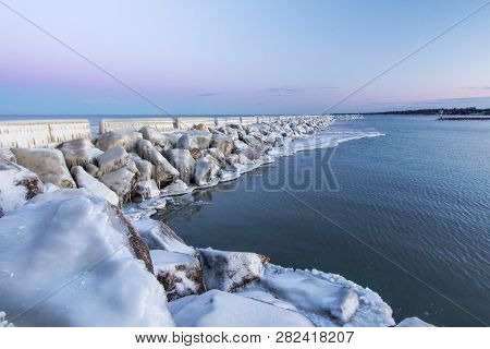 Winter Landscape. Ice Covered Pier On The Michigan Coast Of Lake Huron In Lexington Michigan.