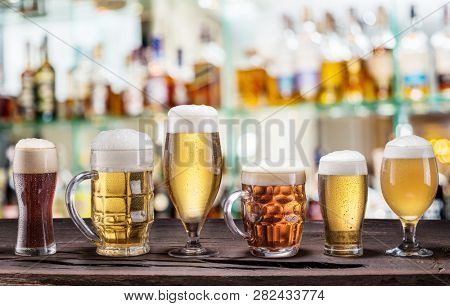 Cold mugs and glasses of beer on the old wooden table. Pub interior and bar counter with beer taps at the background. Assortment of beer.