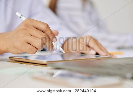 Human Hand With White Plastic Stylo Over Touchpad Screen During Scrolling Through Online Data