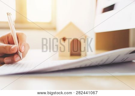 Close Up Hand Of Man Signing Loan Document To Home Ownership. Mortgage And Real Estate Property Inve
