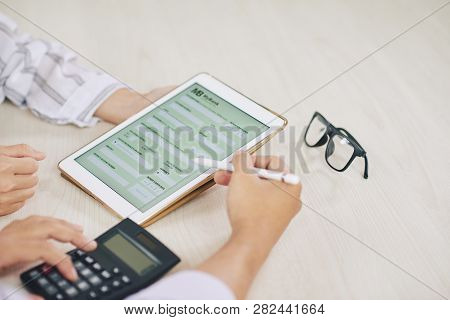 Two Contemporary Auditors Discussing Points Of Application Form Of Credit Report In Touchpad And Mak