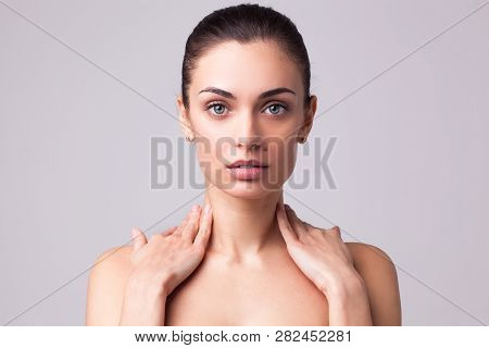 Young Beautiful Brunette Woman With Hands Near Her Neck And Clean Fresh Skin. Closeup Studio Portrai