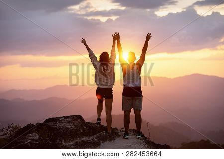 Happy Couple With Raised Arms Stands On Mountain Top Against Sunset And Having Fun In Winner Pose