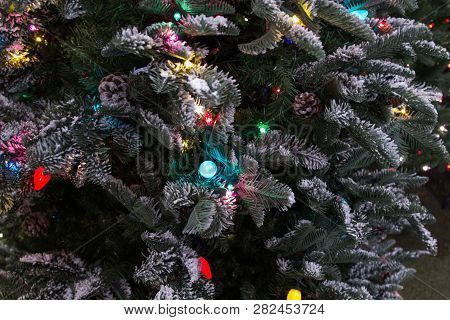 Illuminated Christmas Tree Background. Close Up Of Christmas Tree With Multi Colored Lights And A Du