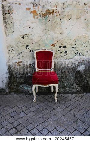 Red old chair before patchy white wall poster