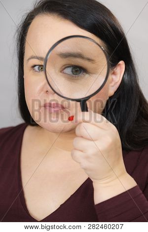 Adult Woman Holding Magnifying Glass Investigating Something And Looking Closely, Trying To Find Sol