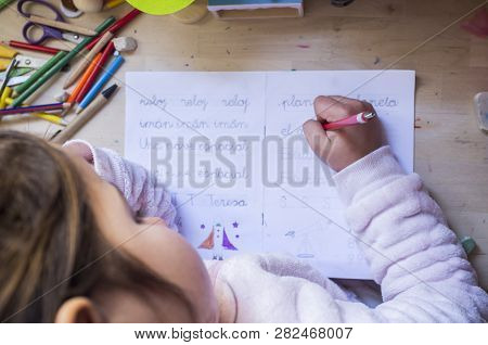 6 Years Old Child Girl Doing Writing Homework In Her Room. Kids Learn To Write Concept