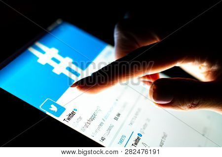 Kharkiv, Ukraine - 12 November 2018: close up girl hand using tablet with Twitter app on the screen with a dark background