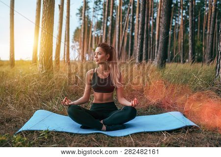 Beautiful And Young Girl Sitting On The Rug In The Lotus Position. Practicing Yoga In Asana Position