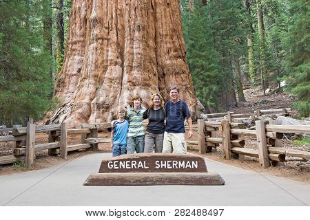 Happy Family Enjoys Posing In Sequoia National Park In Fromt Of General Sherman Sequoia Tree